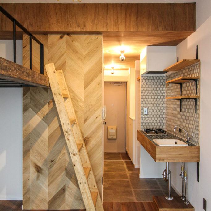 梯子のあるロフトベッドとコンパクトキッチン