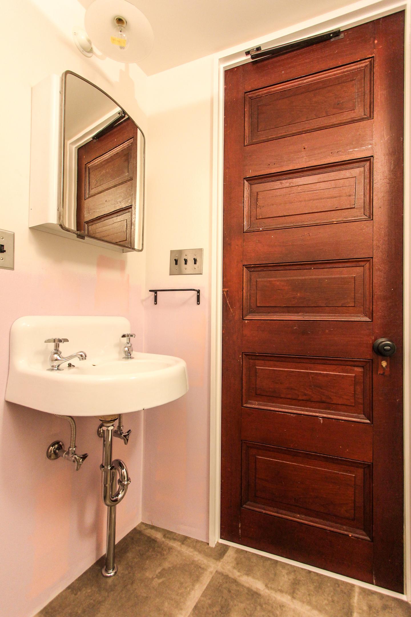 扉とピンク色の壁と洗面ボウル