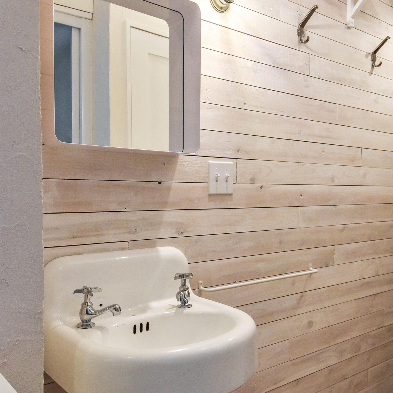 白塗装の木板の壁と手洗器