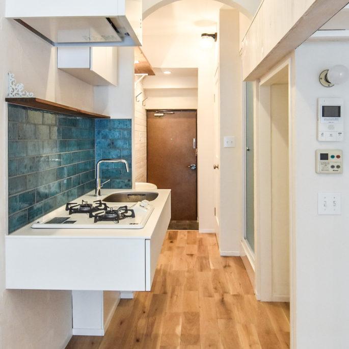 青い壁タイルと白いキッチンとアーチ状の下がり壁