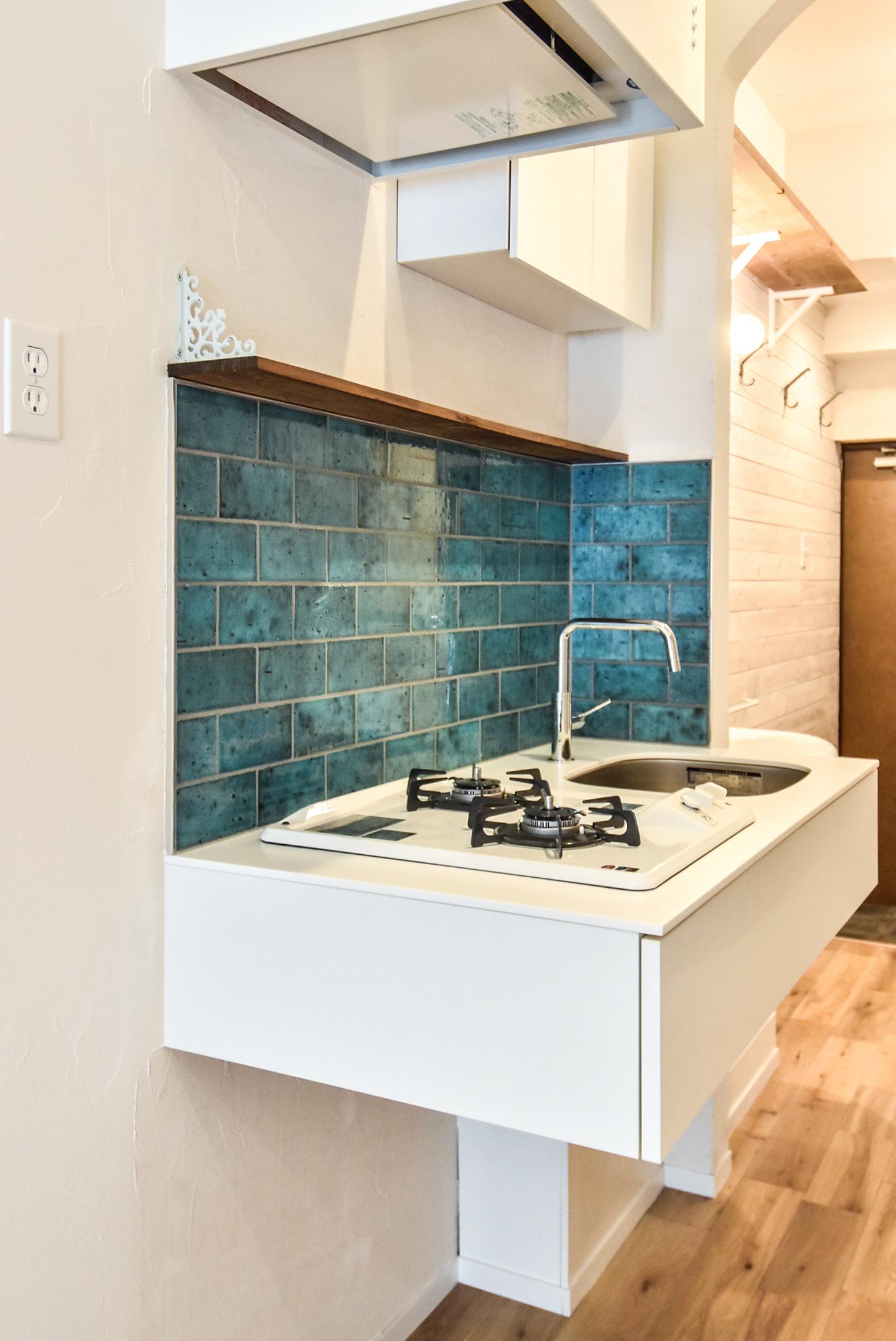 青い壁タイルと白いキッチン