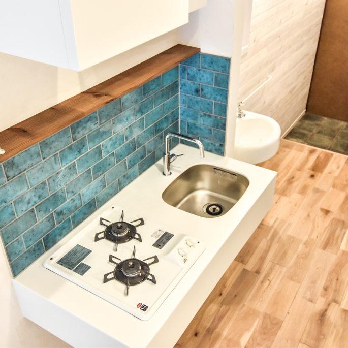 青い壁タイルとフローリングとキッチン