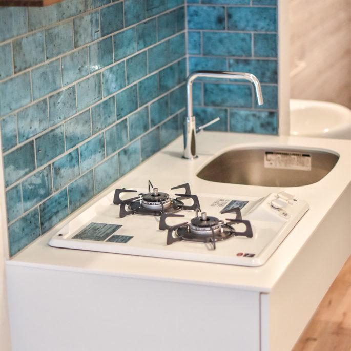 青いタイルの壁と白いミニマルなキッチン
