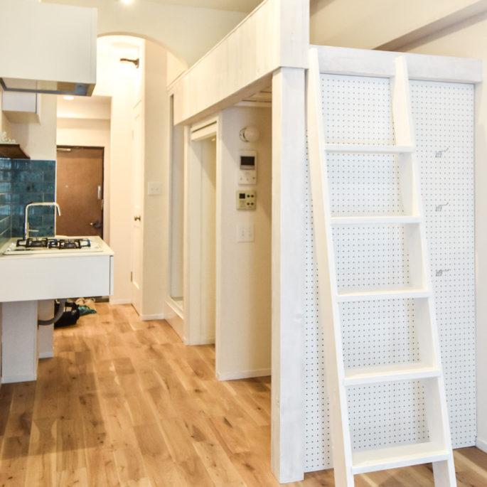 白いロフト梯子と有孔ボードのあるワンルームマンション