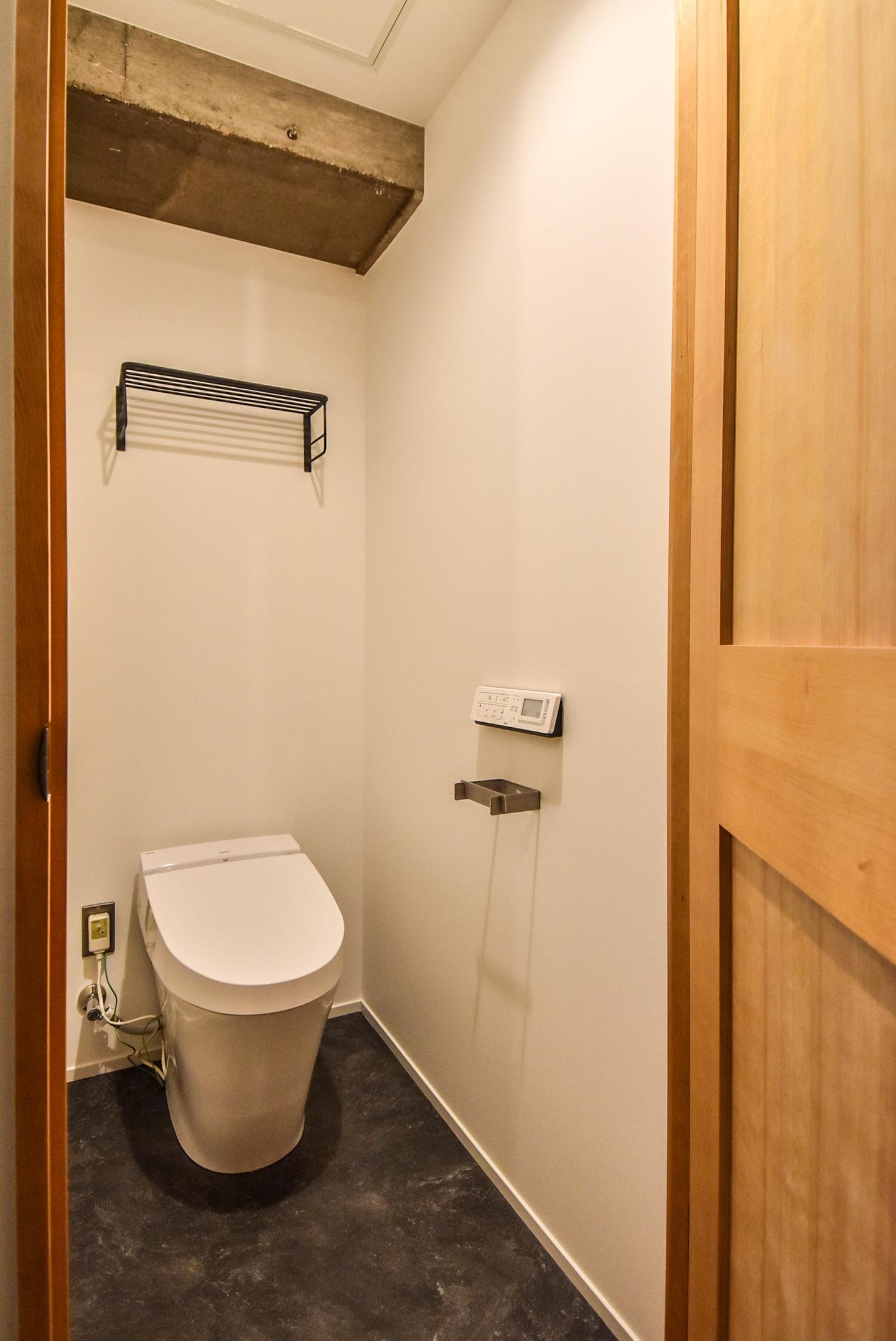 黒い塩ビタイルの床とタンクレスのトイレ
