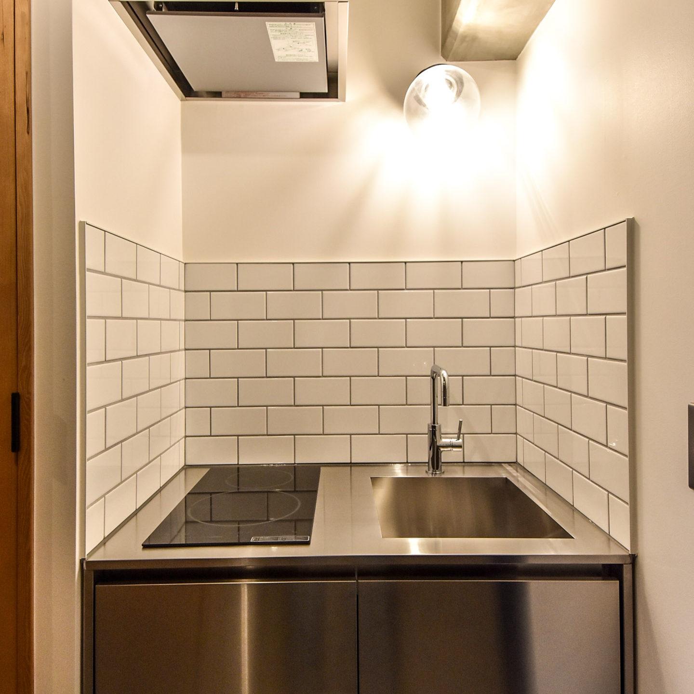 白いタイルと照明とステンレスのキッチン