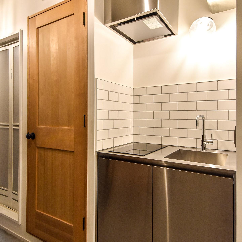 白いタイルと照明とステンレスのキッチンと木製ドア