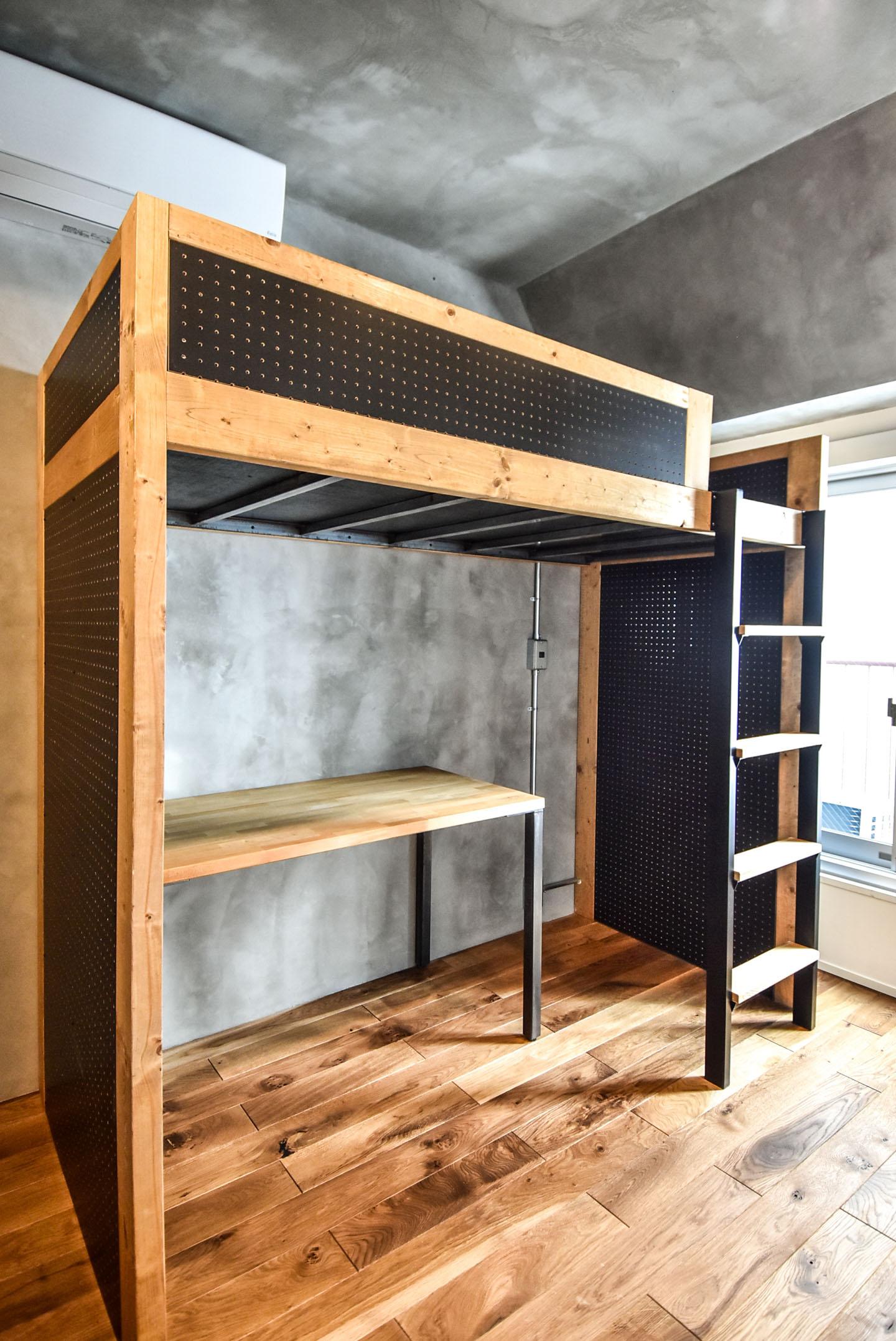 黒い有孔ボードと木のフレームのロフトベッドとデスク